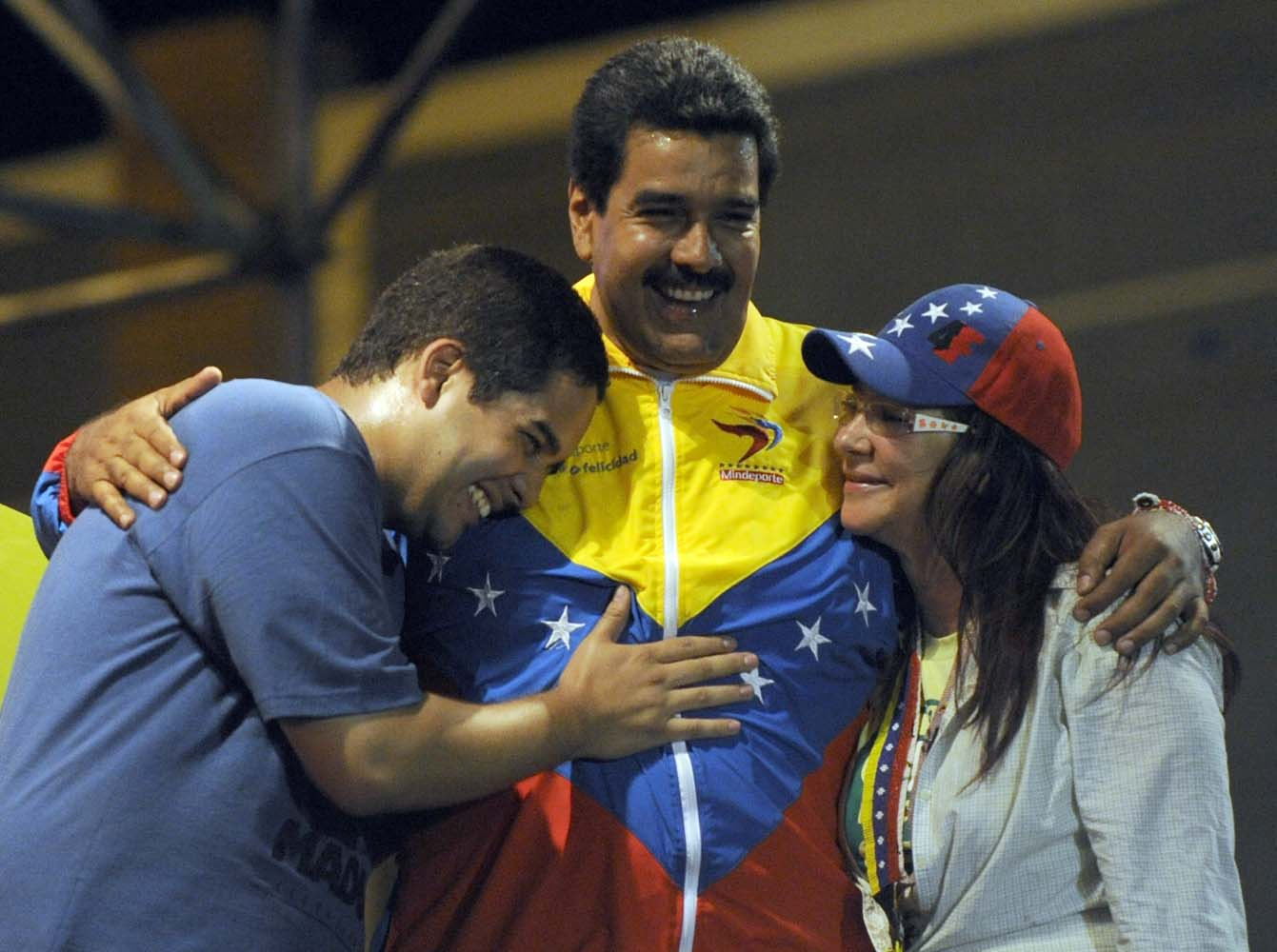 """(FILES) This file picture taken on April 6, 2013 shows Venezuelan acting President Nicolas Maduro (C) embracing his wife Cilia Flores (L) and son Nicolas Maduro during a campaign rally in Puerto Ordaz, Bolivar state, Venezuela. Nicolas Ernesto Maduro Guerra, """"Nicolasito"""", the President's son is an economist and candidate to July 31, 2017 """"constituent assembly"""". / AFP PHOTO / JUAN BARRETO"""