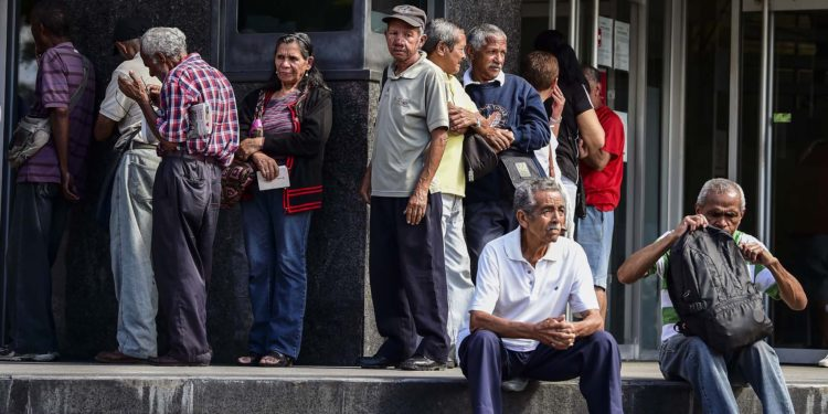 Elderly people wait for their pension monthly payment outside a bank in Caracas, on February 22, 2019. (Photo by RONALDO SCHEMIDT / AFP)