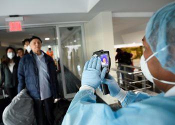 A worker from Ecuador's Health Ministry uses a thermal scanner to check passengers arriving from the U.S., as part of the security measures due to the outbreak of the coronavirus (COVID-19), at Jose Joaquin de Olmedo International Airport in Guayaquil, Ecuador March 13, 2020. REUTERS/Santiago Arcos