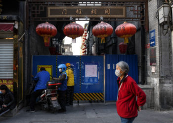 A woman (R) wearing a facemask as a preventive measure against the COVID-19 coronavirus walks past delivery riders waiting to pass food through a hole of a barrier in an alley in Beijing on April 2, 2020. (Photo by GREG BAKER / AFP)