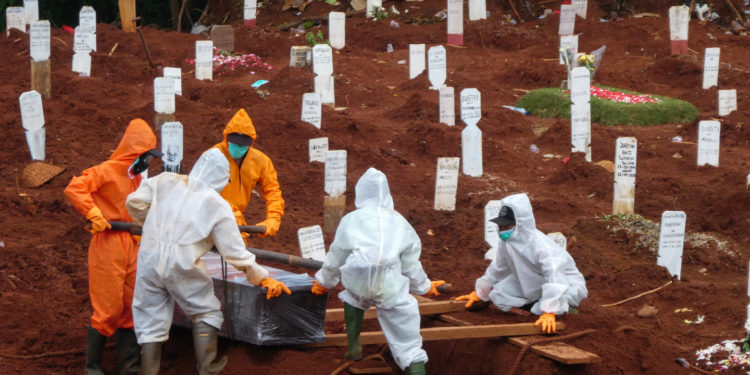 Workers move a coffin of a victim of the COVID-19 coronavirus to a burial site at a cemetery in Jakarta on April 15, 2020. (Photo by BAY ISMOYO / AFP)