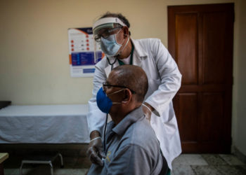 Nicaraguan doctor Javier Nunez checks a patient at a private clinic in Managua on June 3, 2020 amid the new coronavirus pandemic. - Doctors and businessmen in Nicaragua called for a voluntary closure of businesses and quarantine, due to the government's inaction to face the COVID-19 pandemic, but the population did not comply completely for fear of running out of daily sustenance. (Photo by INTI OCON / AFP)