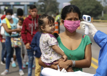 Staffers from the Secretary of Health take the temperature of Venezuelans returning to the country from Colombia, as a preventive measure against the spread of the coronavirus -COVID19- at the Simon Boliviar International Bridge, in Cucuta, Colombia-Venezuela border, on April 4, 2020. - Since the first case of COVID-19 was detected last March 6, Colombia has reported 1,406 people infected and 32 dead. (Photo by Schneyder MENDOZA / AFP)