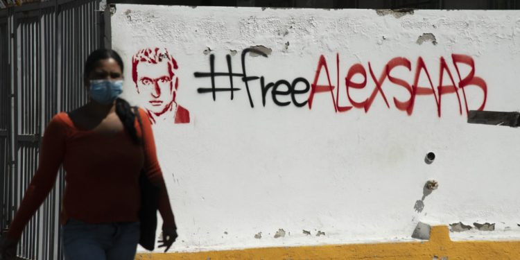 """A pedestrian passes in front of """"Free Alex Saab"""" graffiti """" in Caracas, on Feb. 4. Photographer: Carlos Becerra/Bloomberg"""